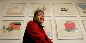 "BW_062206Annie01_ Annie Pootoogook is framed by her artwork on display at the Powerplant, Toronto, June 22, 2006. Her favourite piece is called ""Pitseolak Drawign with Two Girls on the Bed"". In the painting are Annie's grandmother, her mother Napachie and herself._(Bernard Weil/Toronto Star) (Photo by Bernard Weil/Toronto Star via Getty Images)"